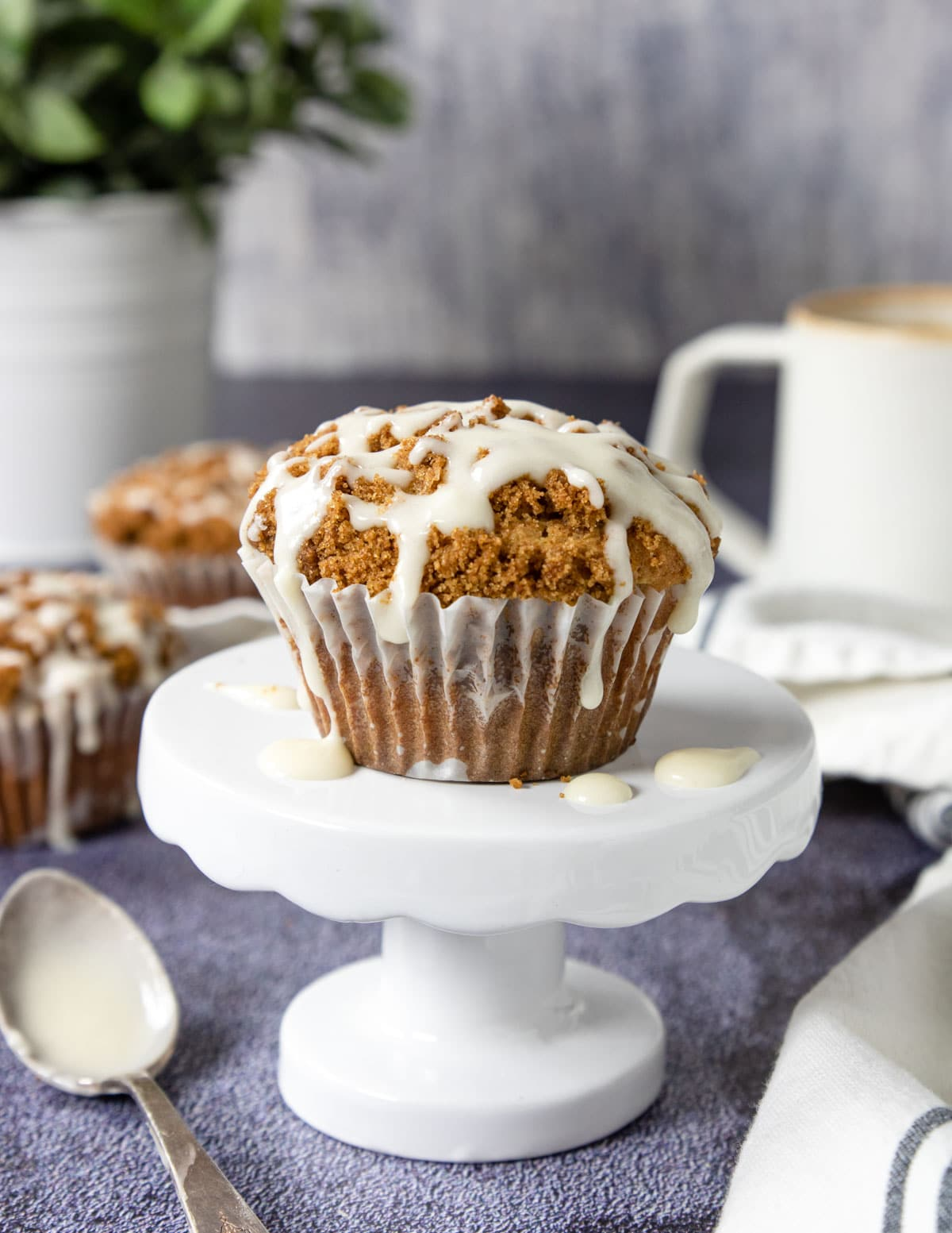 coffee cake muffin on a white cake plate, white glaze drizzled and dripping over the sides