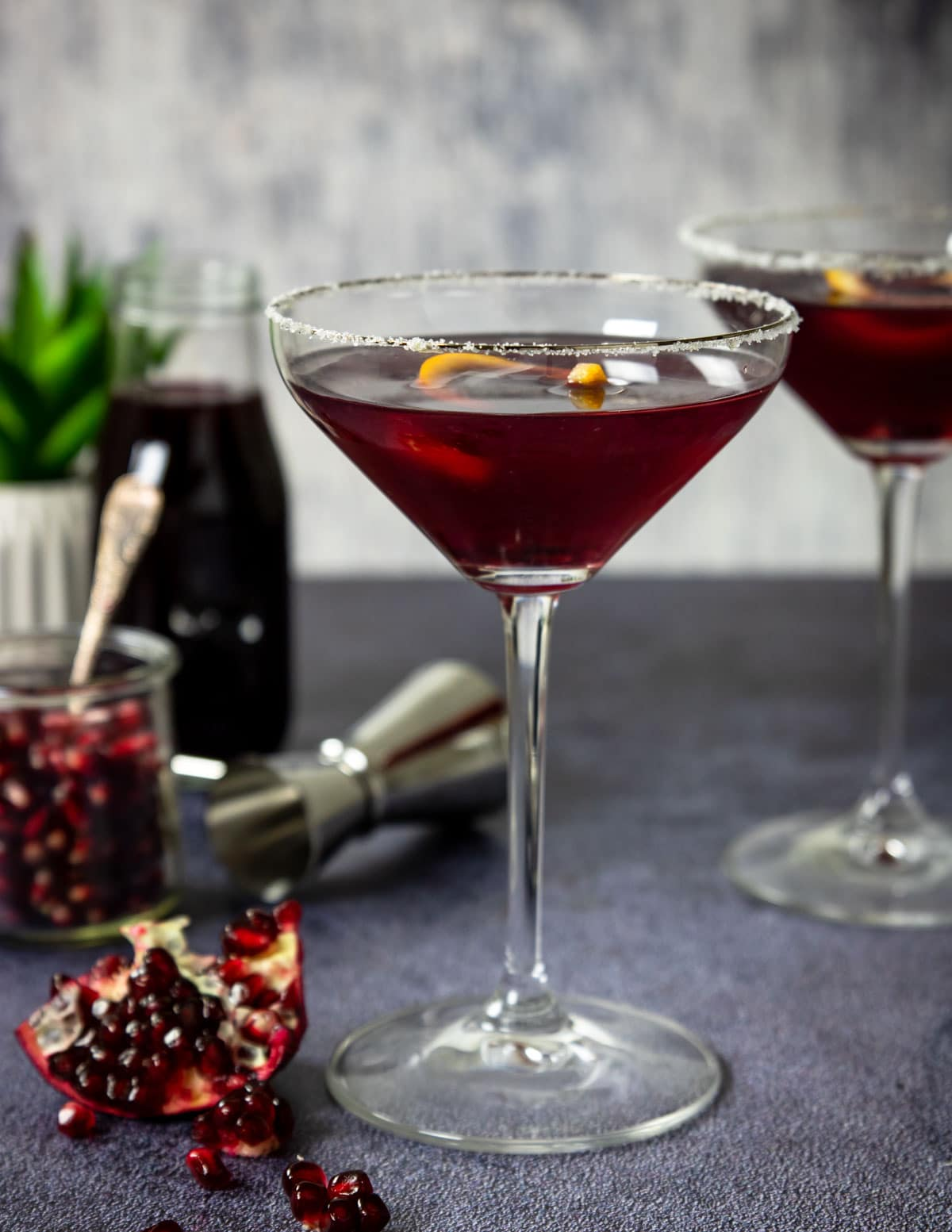 pomegranate martini with a sugar rim and pomegranate arils on the table