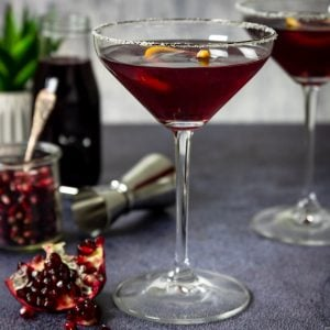 pomegranate martini in a stemmed glass with and orange twist