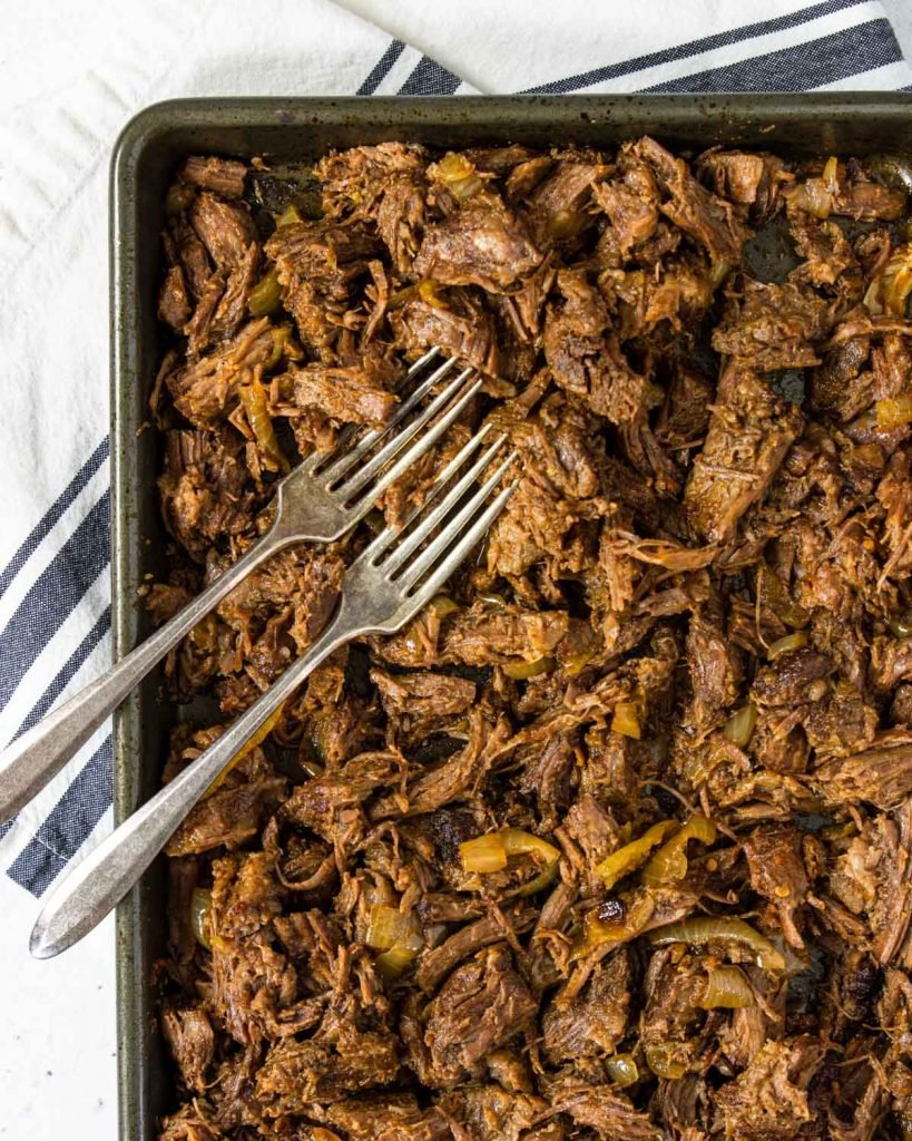 a baking sheet filled with shredded mexican beef