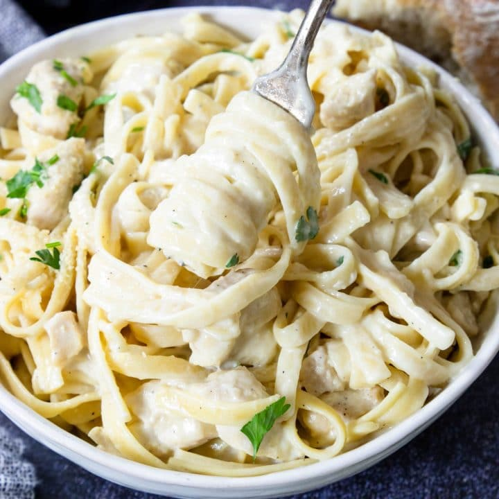 a white bowl of the very best chicken alfredo that is creamy and cheesy, being twirled on a fork