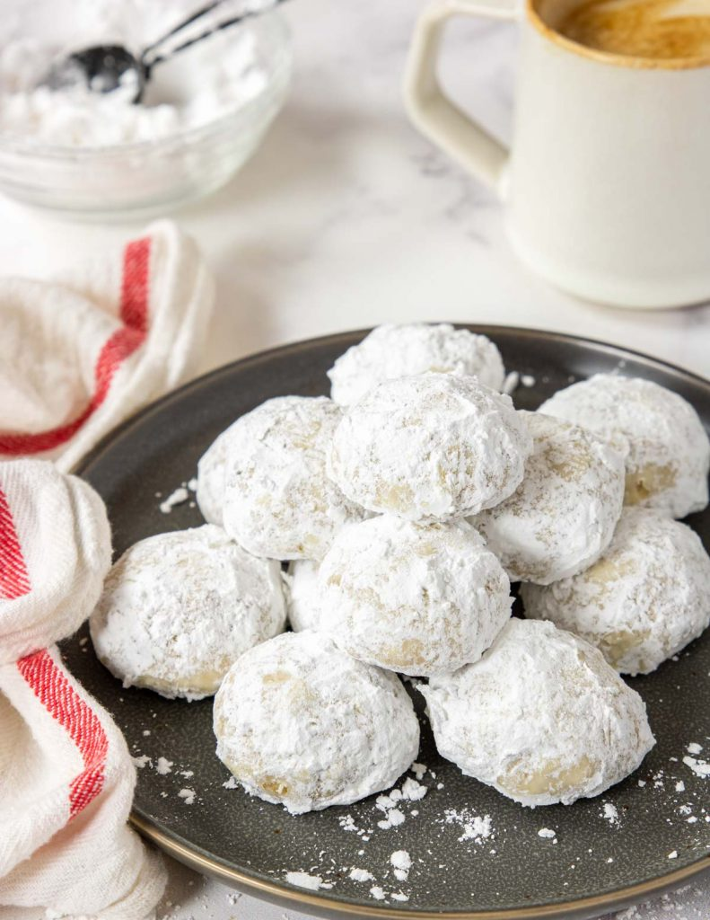 a grey plate filled with pecan snowball cookies with a cup of coffee in the background