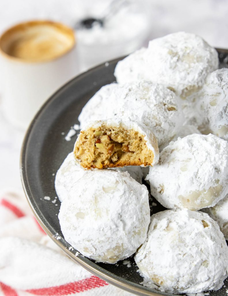 A pile of pecan snowball cookies with one broken in half