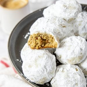 a pecan snowball cookie that is broken in half to see the middle