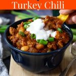 turkey chili in a bowl topped with green onions and sour cream with Pinterest text