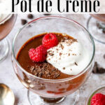 Chocolate pot de creme in a dessert cup with whipped cream and raspberries