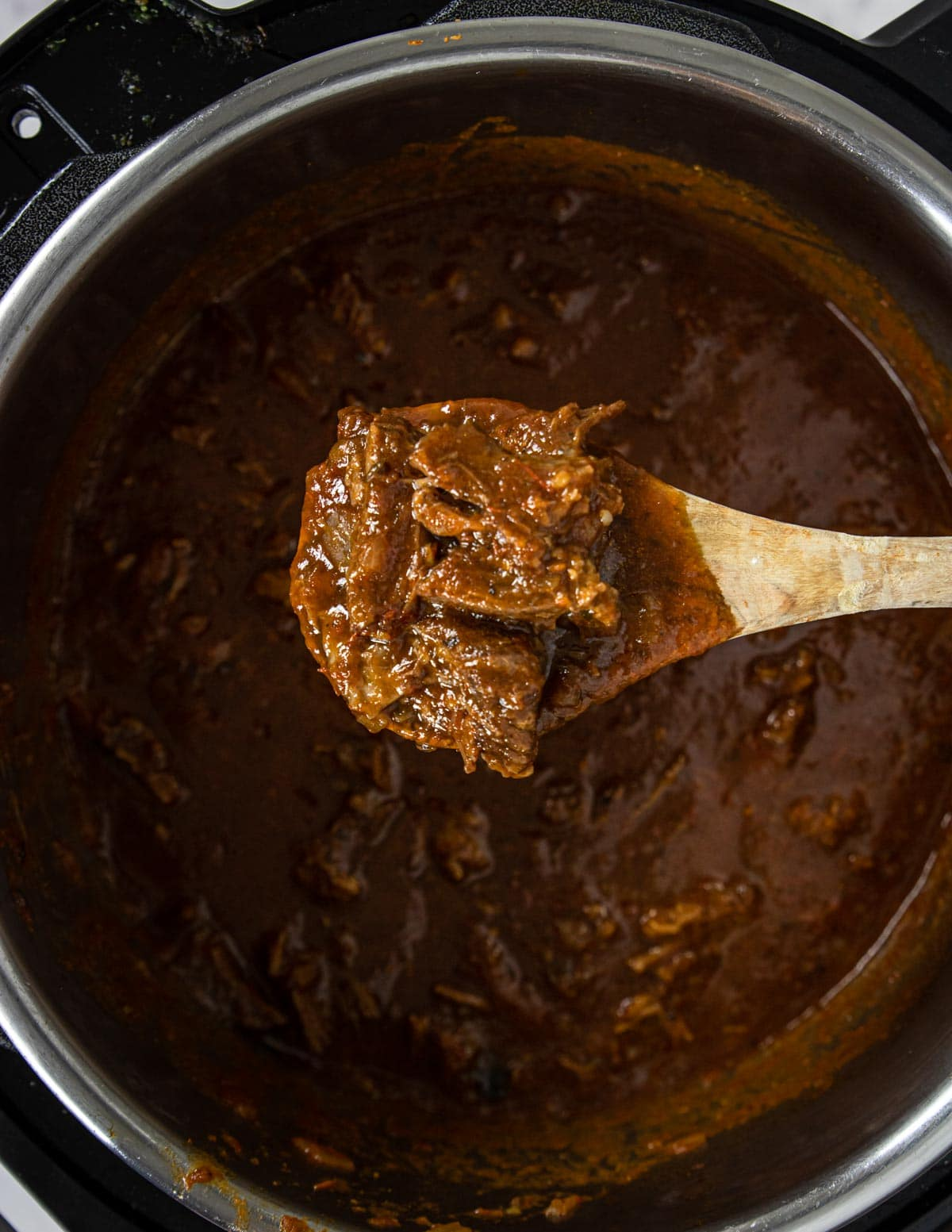 beef ragu on a wooden spoon over an instant pot
