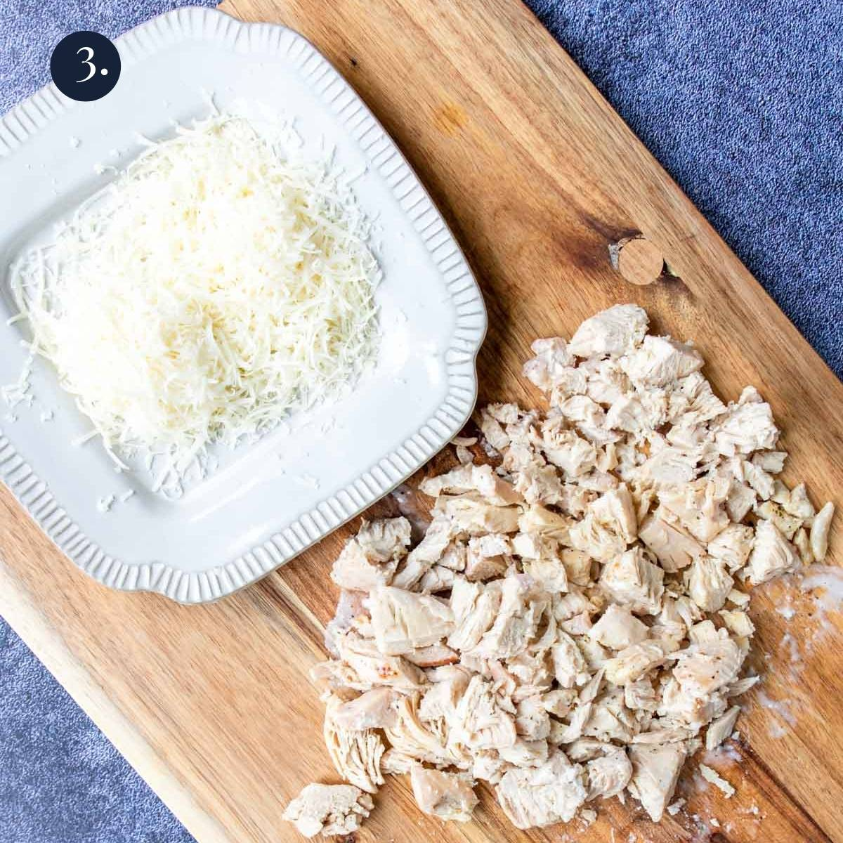 chicken cut into pieces and parmesan shredded on a cutting board