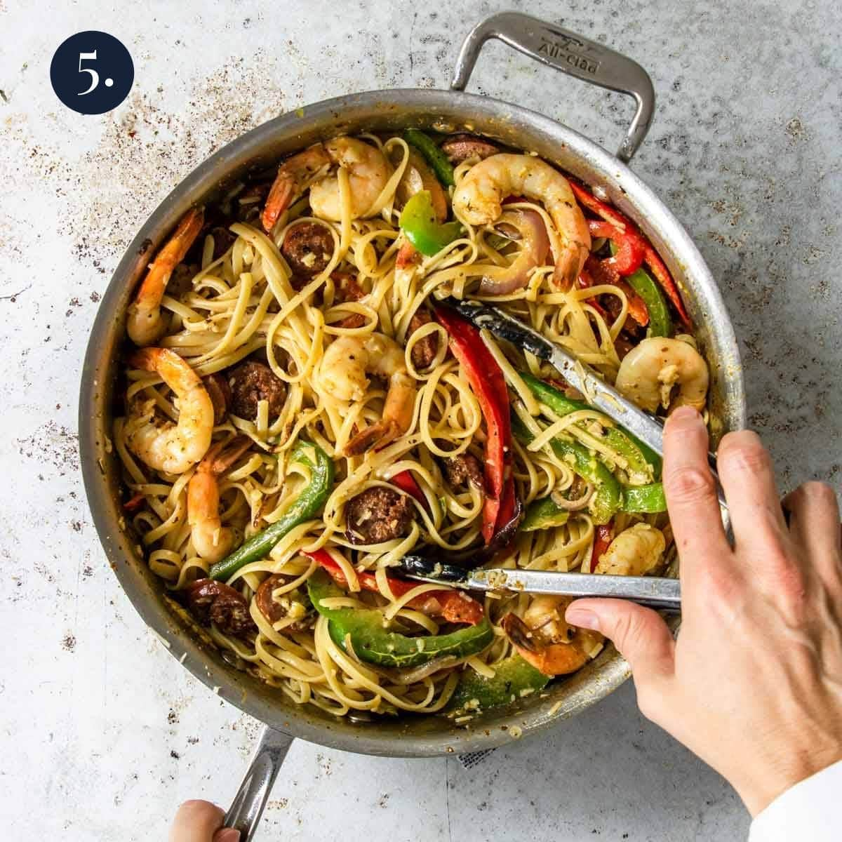 tossing pasta with shrimp, peppers, and sausage