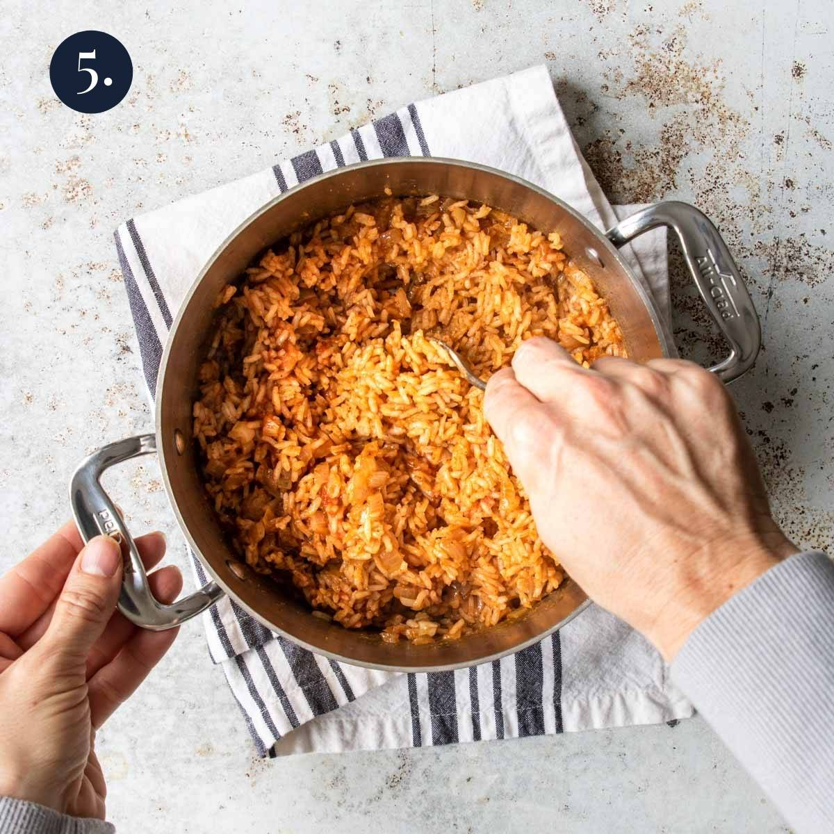 fluffing red rice in a pot with a fork