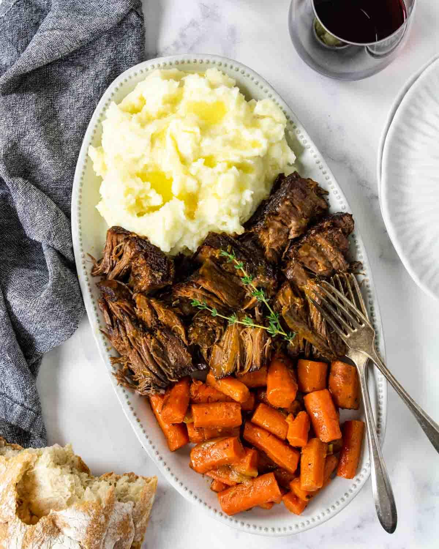 a serving platter of beef pot roast, carrots and potatoes.