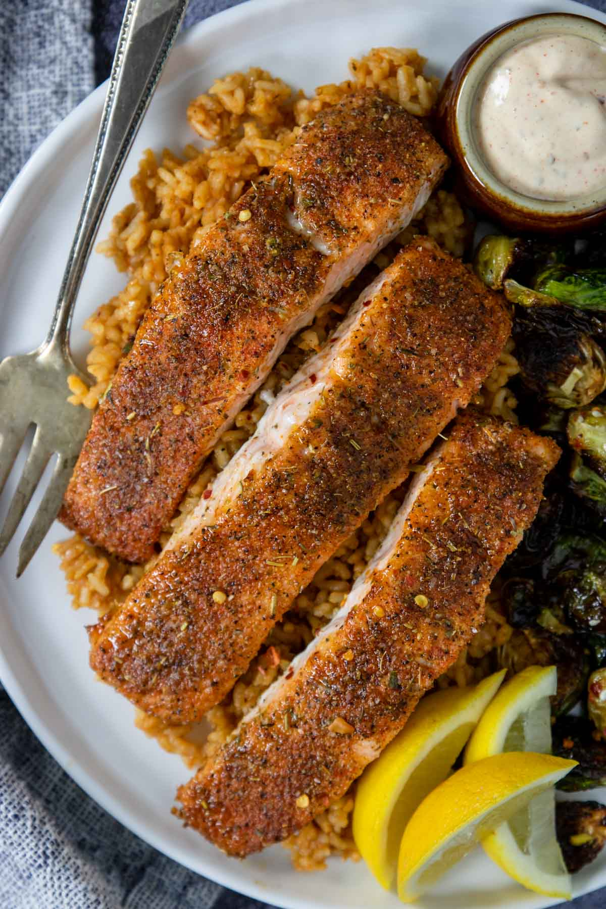 Baked Cajun salmon on a plate with rice and lemon wedges