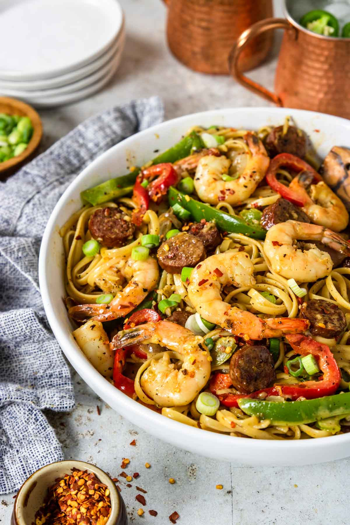 a bowl of pasta with shrimp, sausage and peppers topped with green onions