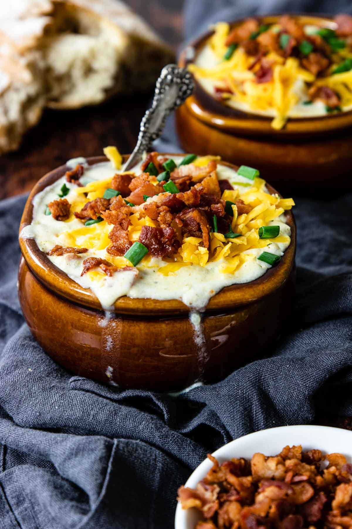 a bowl of creamy soup topped with cheese, bacon and onions