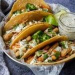 a tray of fish tacos with tartar sauce