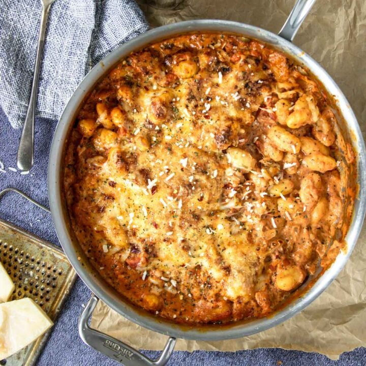 A skillet full of baked gnocchi with sauce and cheese