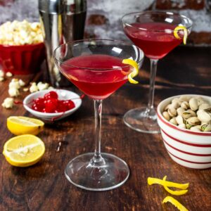 run it back cocktail in a martini glass on a table with snacks