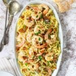 Shrimp and pasta on a serving platter with parsley and parmesan