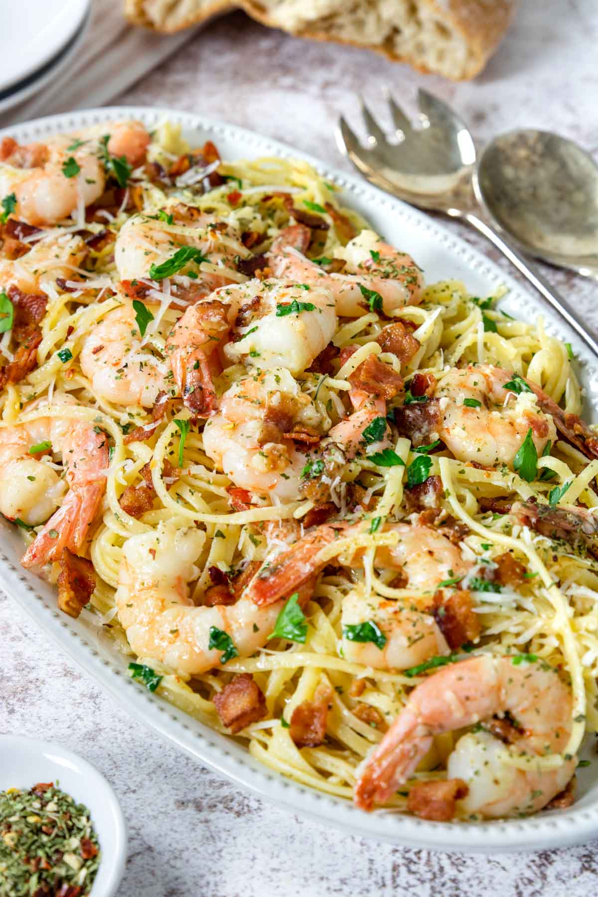 a platter with shrimp carbonara, table bread and serving utensils