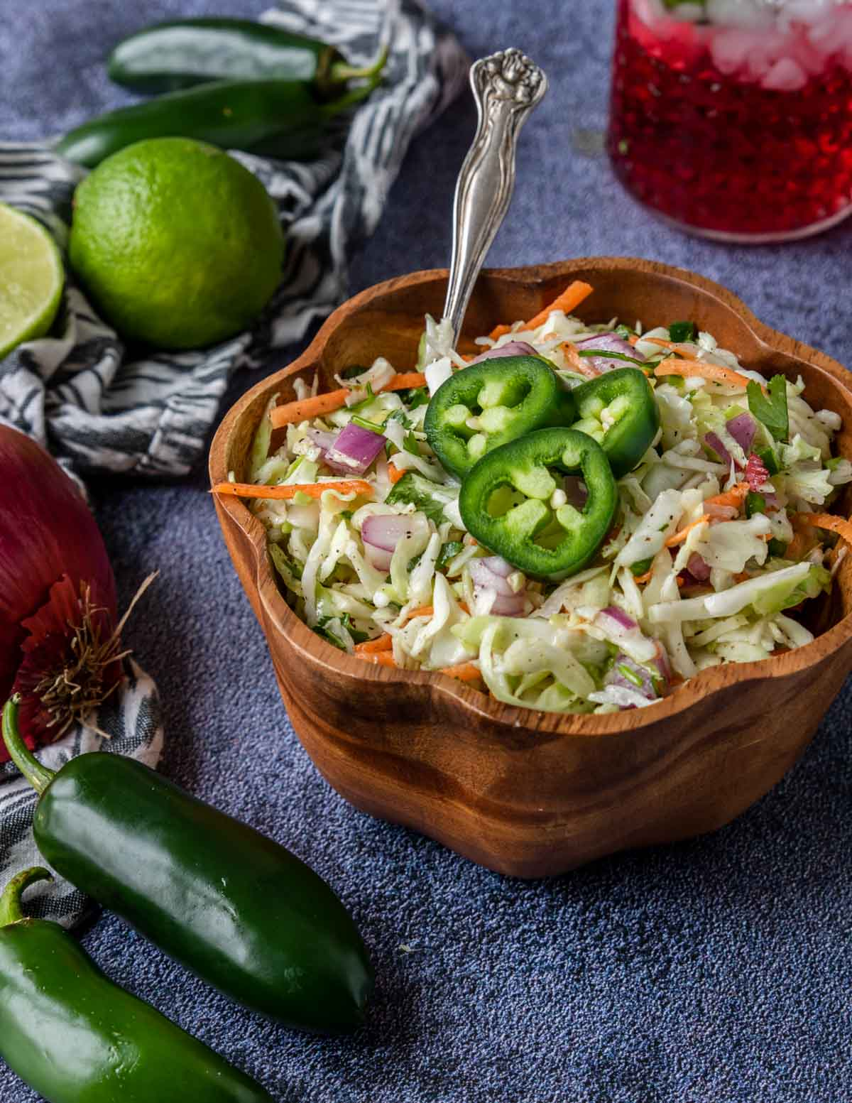 cilantro lime slaw topped with jalapeno in a wooden bowl
