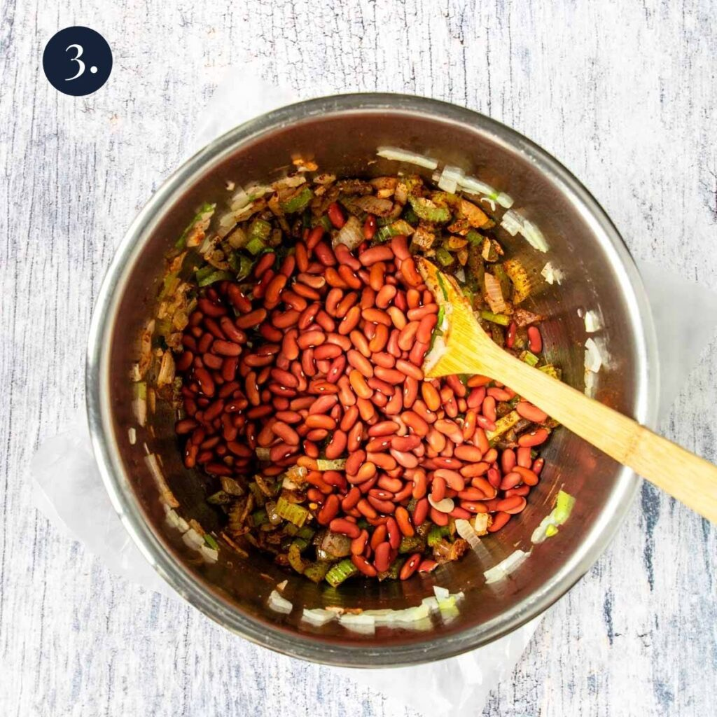 dry red beans in the instant pot over celery and onions