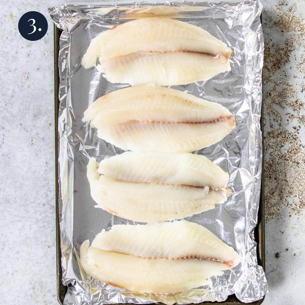 4 fish fillets on a foil lined baking pan
