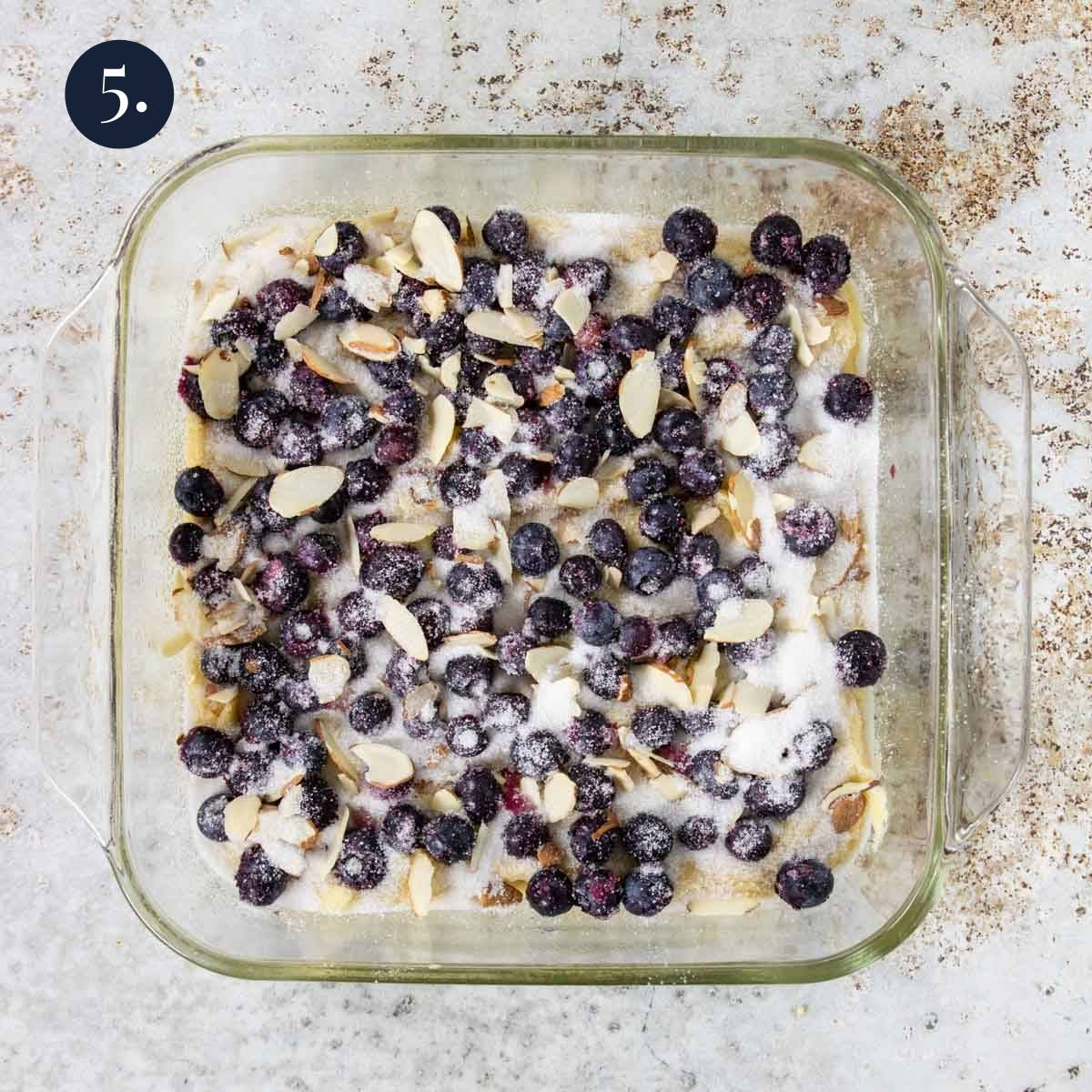 cake batter topped with blueberries, almonds and sugar