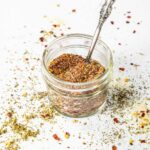a jar of seasonings with spices and herbs spilled around