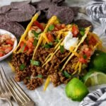 four ground beef tacos on a table with all the toppings