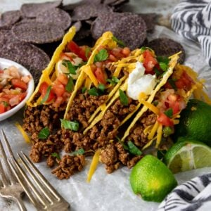 four ground beef tacos in a row with pico de gallo and sour cream