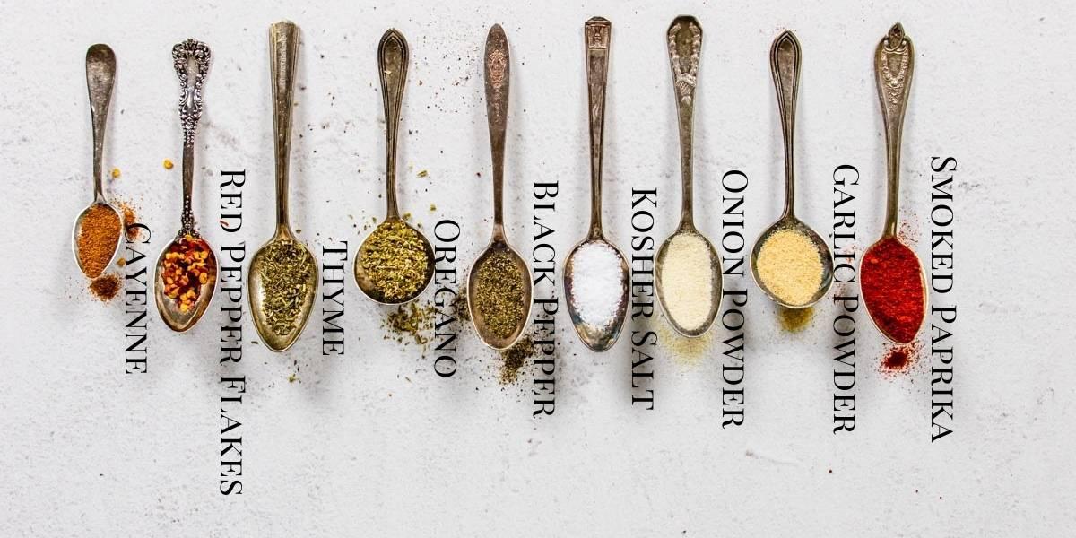 ingredients for cajun seasoning on spoons in a row