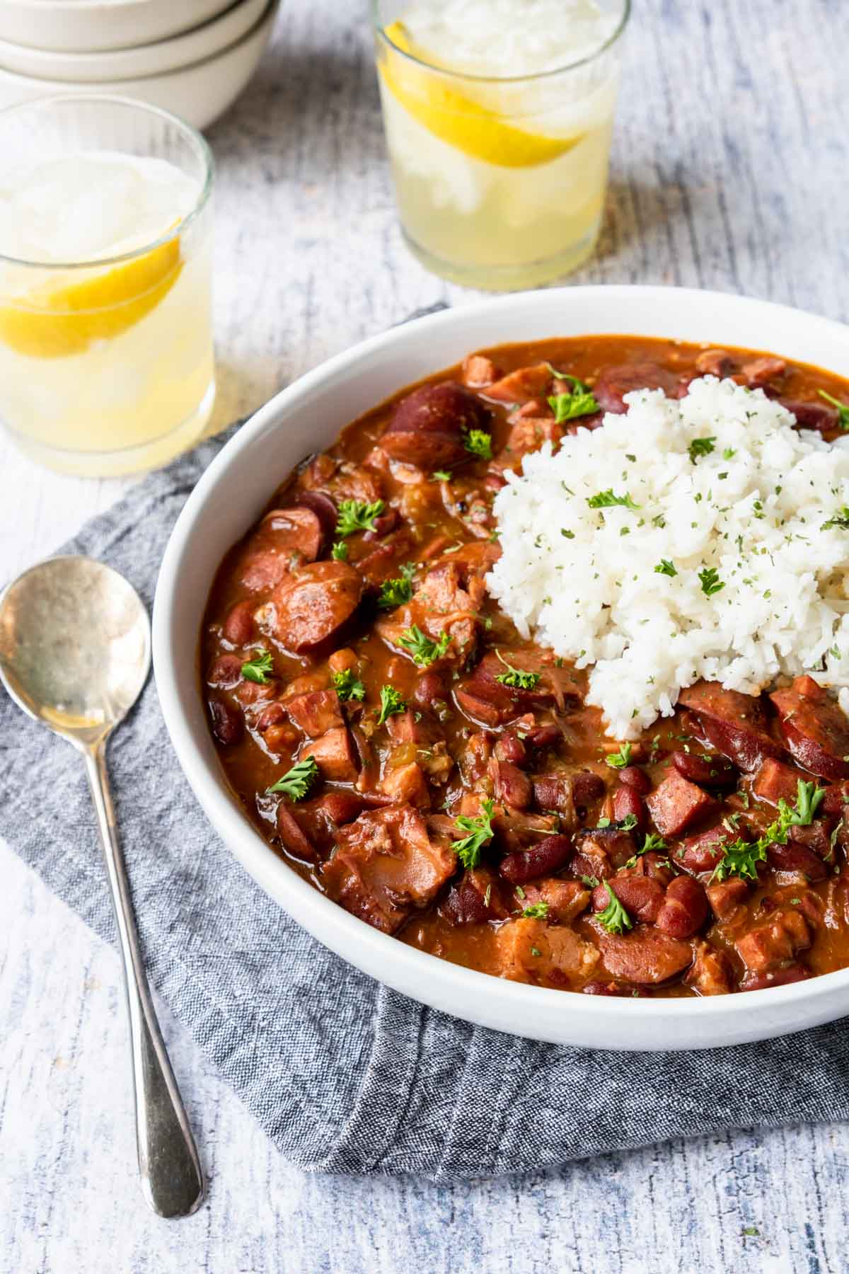 a large bowl of red beans and rice and two glasses of lemonade