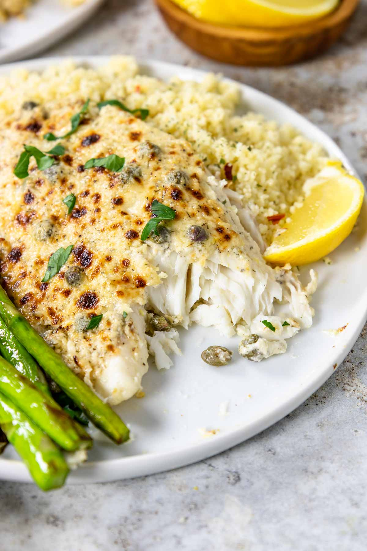 flaky tilapia with a parmesan topping and a lemon wedge