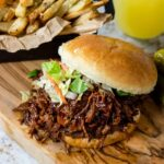 Shredded BBQ Beef Sandwich with fries and a soda