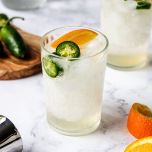 a cocktail glass with tequila, orange and jalapeno
