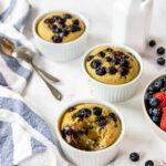baked steel cut oats with blueberries drizzled with syrup, fresh fruit to the side