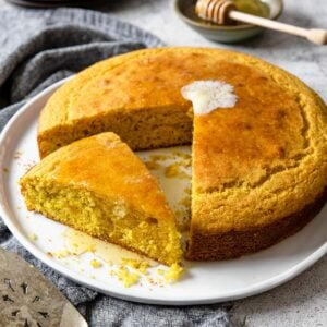 cornbread with a sliced turned to the side and covered in honey
