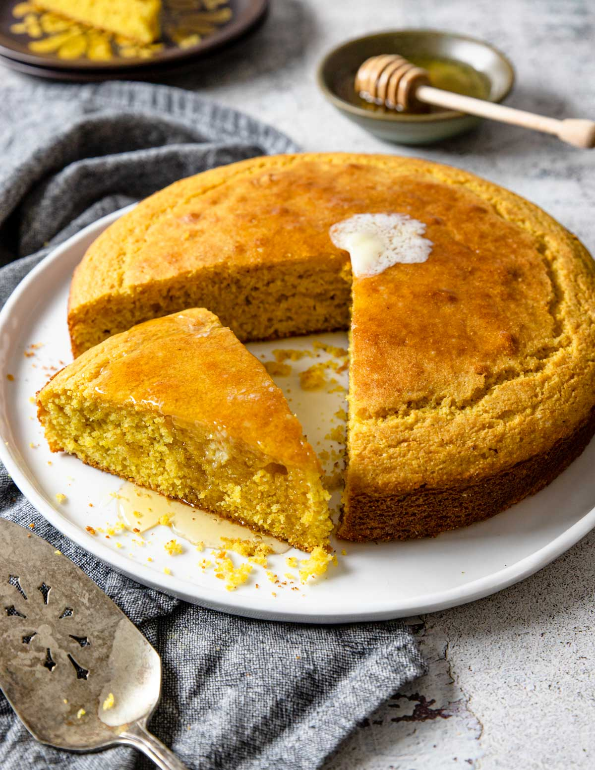 cornbread round with a pat of butter on top, and a slice angled out of the cornbread
