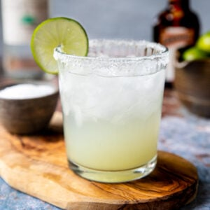 a salt rimmed glass with a classic margarita garnished with a lime