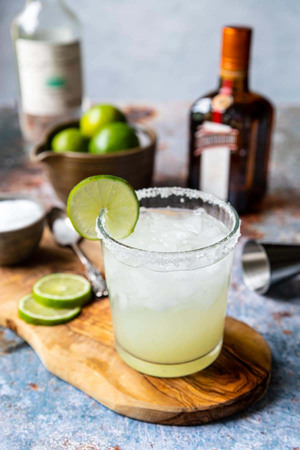a classic margarita in a rocks glass with a salt rim and a lime wheel