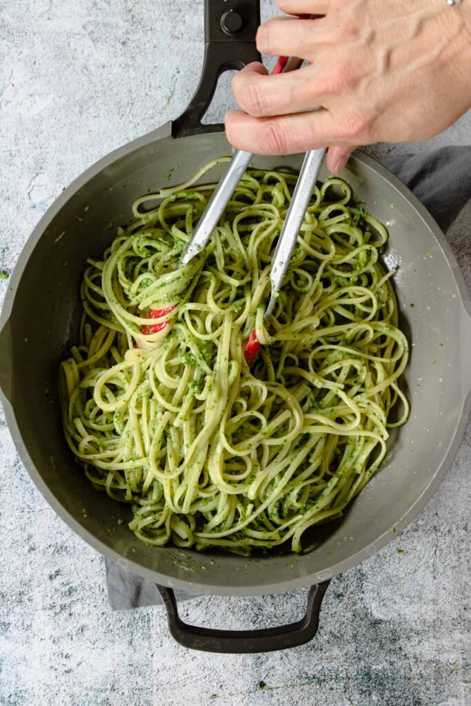 a skillet with pasta being tossed with pesto