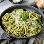 a big bowl of pesto pasta topped with parm cheese