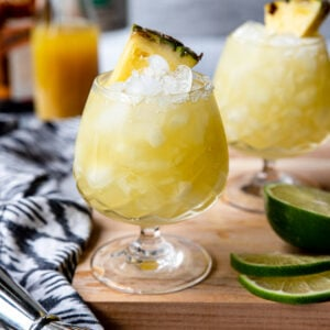 pineapple margarita in an etched glass, garnished with a pineapple wedge