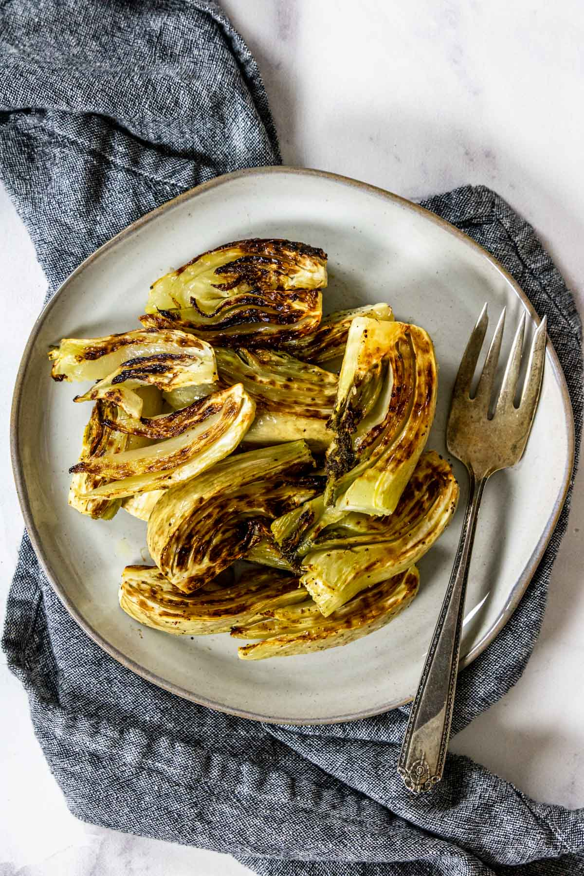 roasted fennel wedges on a plate with a serving fork