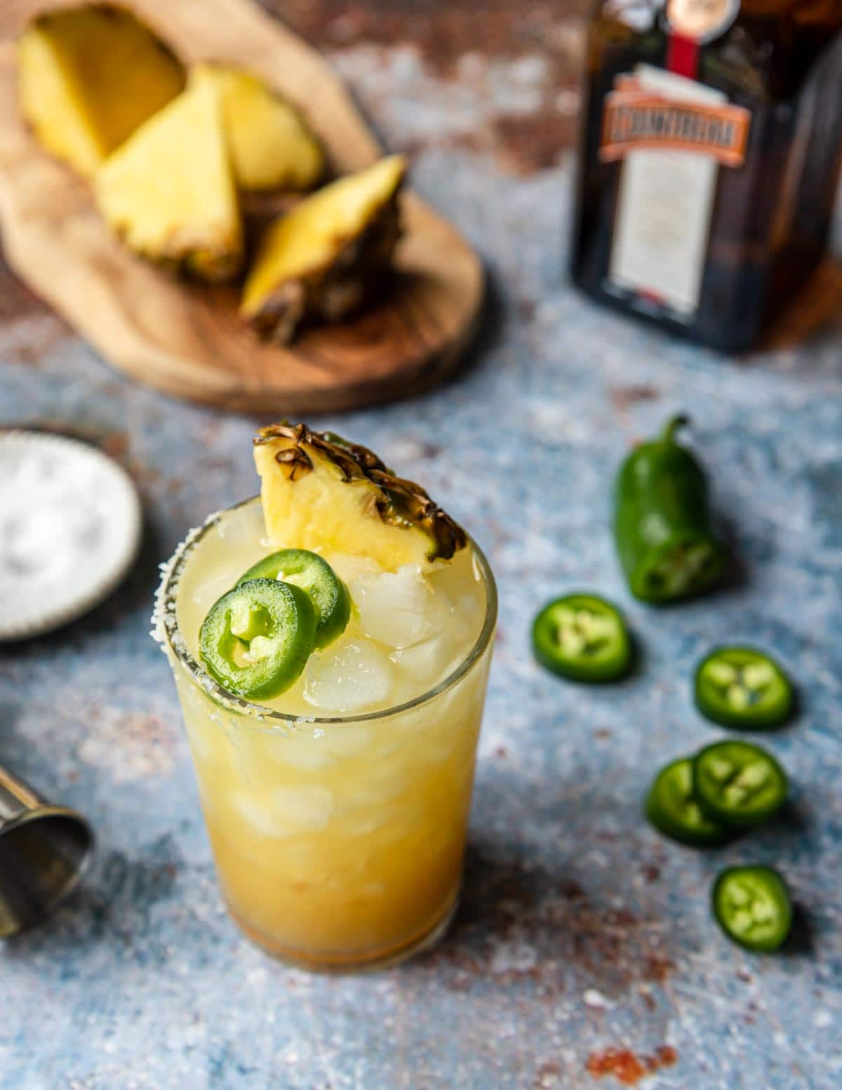 a glass of pineapple jalapeno margarita garnished with pineapple and jalapeno