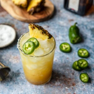 pineapple jalapeno spicy margarita in a glass with jalapenos to the side