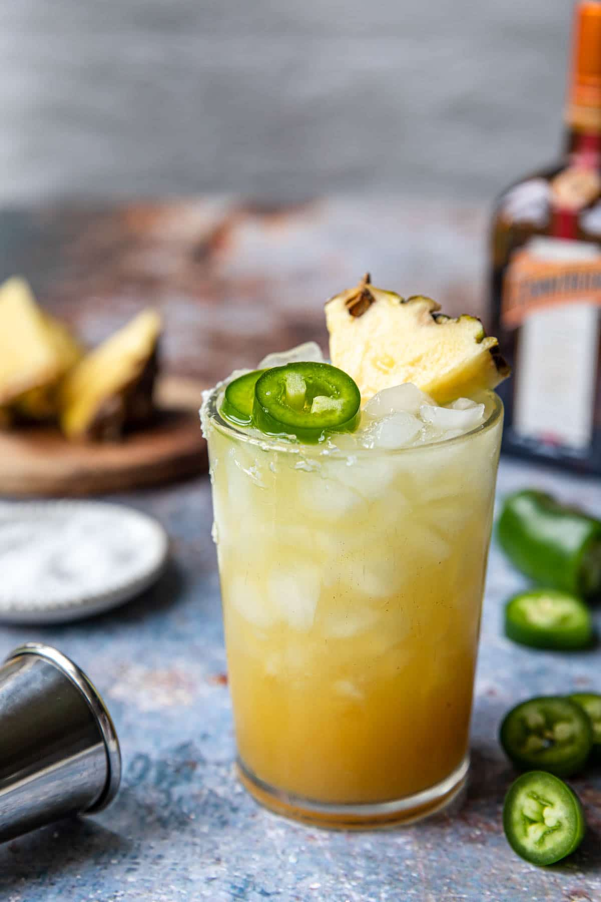 a spicy margarita garnished with pineapple wedge and jalapenos