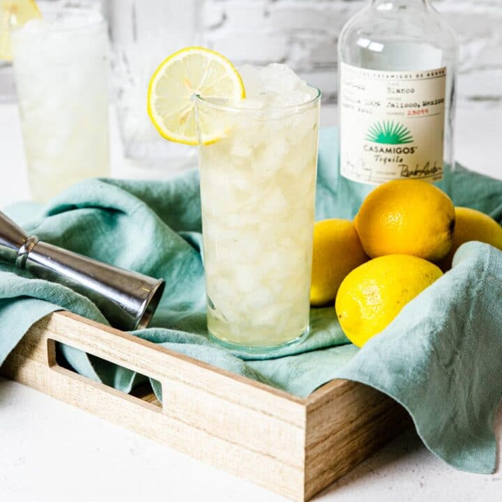Tequila lemonade in a tall glass with a bottle of tequila to the side