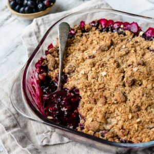a pan of blueberry crumble with a spoonful taken out.