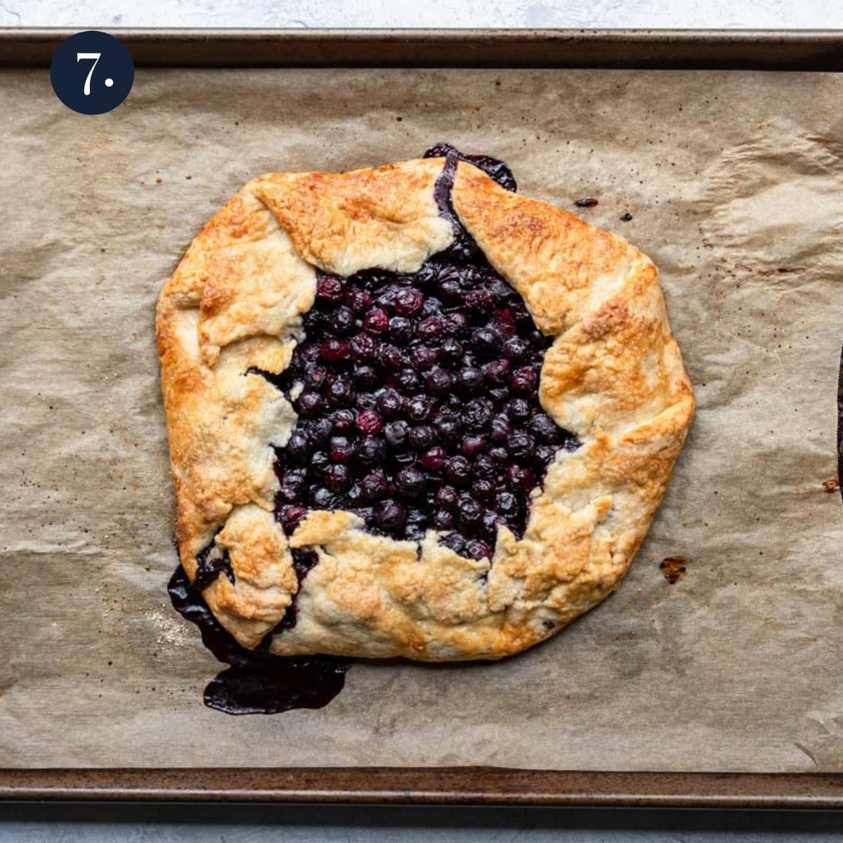 a blueberry galette on a baking sheet with parchment paper